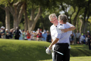 Photo - Colin Montgomerie, left, hugs Gene Sauers following Montgomerie's putt on the 18th hole during a 3-hole playoff in the final round of the U.S. Senior Open golf tournament at Oak Tree National in Edmond, Okla., Sunday, July 13, 2014. Photo by Sarah Phipps, The Oklahoman
