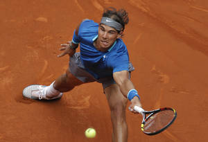 Photo - Rafael Nadal from Spain returns the ball during a Madrid Open tennis tournament match against Juan Monaco from Argentina, in Madrid, Spain, Wednesday, May 7, 2014. (AP Photo/Andres Kudacki)