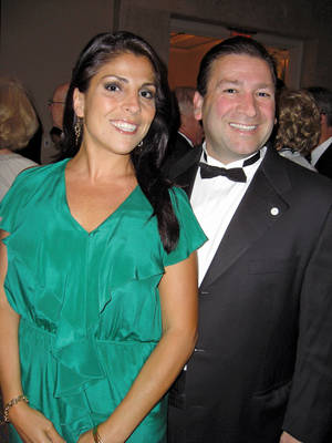 "Photo -   In this May 16, 2011 photo Dr. Scott Kelley, right, and his wife Jill Kelley pose for a photo in Tampa, Fla. Jill Kelley's attempt to climb the Tampa social ladder _ the rungs of which included some high-ranking military officials _ has come to an ignominious halt. Accounts of lavish parties at her bayfront mansion have been replaced by reports of her family's financial woes and other dirty laundry, and claims that she traded on her acquaintance with David Petraeus to try to further lucrative business dealings. Now, even her ""Friends of MacDill"" Air Force base access pass has been unceremoniously revoked. (AP Photo/Tampa Bay Magazine) MANDATORY CREDIT"