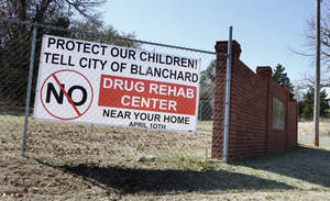 Photo - Top:  A protest sign is posted on a fence about a mile from Second Story Ranch .   Signs, posted around the area, remind residents of a planning commission meeting in Blanchard on Thursday.  Photos by Steve Sisney,  The Oklahoman <strong>STEVE SISNEY -   </strong>