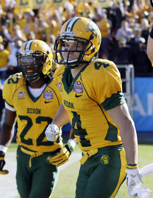 Photo - FILE - In this Jan. 4, 2014 file photo, North Dakota State's Ryan Smith (4) is seen during of the FCS championship NCAA college football game in Frisco, Texas. The former Wahpeton High School and NDSU standout is continuing his career north of the border. It was announced Monday, April 14, 2014, that Smith, a 5-foot-7, 175-pound receiver signed with the Saskatchewan Roughriders of the Canadian Football League. Details of the contract weren't released. (AP Photo/Tony Gutierrez, File)