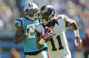 Photo - St. Louis Rams' Tavon Austin (11) runs past Carolina Panthers' Josh Thomas (22) in the first half of an NFL football game in Charlotte, N.C., Sunday, Oct. 20, 2013. (AP Photo/Mike McCarn)