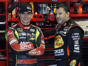 Photo - Drivers Jeff Gordon, left, and Tony Stewart talk in the garage during practice for Sunday's NASCAR Sprint Cup Series auto race, Friday Aug. 2, 2013, in Long Pond, Pa. (AP Photo/Russ Hamilton Sr.)