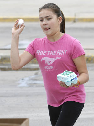 Photo - Brannah Talamantes, 11, throws an egg filled with paint at a piece of paper during an art activity at the Almonte Library. Such activities will continue throughout the summer. Photo By Steve Gooch, The Oklahoman <strong>Steve Gooch - The Oklahoman</strong>