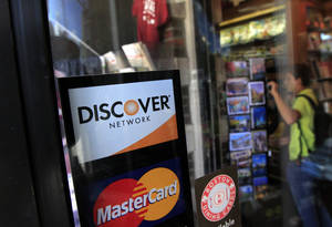 Photo -   A Discover logo is adhered to a window at the entrance of a shop in Cambridge, Mass., Monday, Sept. 24, 2012. Discover Bank is paying $214 million to settle charges that it pressured credit card customers to buy costly add-on services like payment protection and credit monitoring. (AP Photo/Steven Senne)