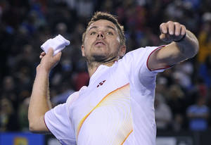 Photo - Stanislas Wawrinka of Switzerland throws a wristband to the spectators after defeating Novak Djokovic of Serbia in their quarterfinal at the Australian Open tennis championship in Melbourne, Australia, Tuesday, Jan. 21, 2014.(AP Photo/Andrew Brownbill)