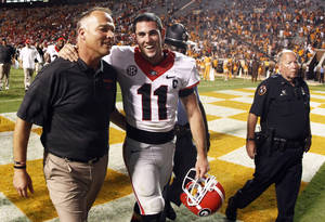 Photo - Georgia head coach Mark Richt walks off the field with quarterback Aaron Murray (11) after defeating Tennessee 34-31 in overtime of an NCAA college football game on Saturday, Oct. 5, 2013, in Knoxville, Tenn. (AP Photo/Wade Payne)