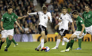photo -   Germany's Thomas Muller, centre, holds off a challenge from Republic of Ireland's Darren O'Dea, left, and Seamus Coleman, right, during their World Cup Group C qualifying soccer match at the Aviva Stadium, Dublin, Ireland, Friday, Oct. 12, 2012. (AP Photo/Peter Morrison)