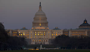Photo - The setting sun is reflected in the windows of the U.S. Capitol, on Capitol Hill, Friday, March 22, 2013 in Washington. (AP Photo/Alex Brandon)