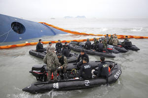 Photo - South Korean rescue team members prepare to search for passengers of a ferry sinking off South Korea's southern coast, in the water off the southern coast near Jindo, south of Seoul, South Korea, Thursday, April 17, 2014. Fears rose Thursday for the fate of more than 280 passengers still missing more than 24 hours after their ferry flipped onto its side and filled with water off the southern coast of South Korea. (AP Photo/Yonhap) KOREA OUT