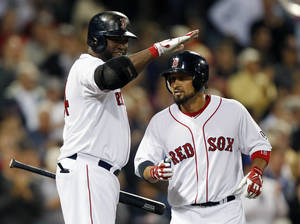 Photo - Boston Red Sox's David Ortiz, left, pats teammate Shane Victorino on the head after Victorino's solo home run in the sixth inning of a baseball game against the Baltimore Orioles in Boston, Thursday, Aug. 29, 2013. (AP Photo/Michael Dwyer)