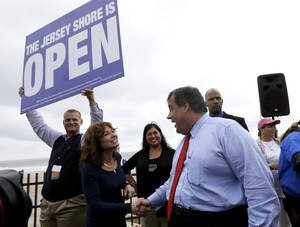 Photo - New Jersey Gov. Chris Christie, right, talks to Carla Pilla, of Seaside Heights, N.J., while Robert Hilton, left, executive director of the Jersey Shore Convention and Visitor's Bureau, holds a sign, Friday, May 24, 2013, in Seaside Heights, N.J. Christie cut a ribbon to symbolically reopen the state's shore for the summer season, seven months after being devastated by Superstorm Sandy. Several beach communities have annual beach ribbon cuttings, announcing they are back in business. But this year's ceremonies are more poignant seven months after a storm that did an estimated $37 billion of damage in the state. (AP Photo/Julio Cortez)