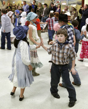 Photo - Students at Chisholm Elementary School do the Virginia Reel and other dances during a hootenanny at the school in Edmond, OK, Friday, April 26, 2013,  By Paul Hellstern, The Oklahoman
