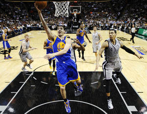 Photo - Golden State Warriors' Klay Thompson (11) scores as San Antonio Spurs' Danny Green (4) defends during the first half of Game 2 in their Western Conference semifinal NBA basketball playoff series, Wednesday, May 8, 2013, in San Antonio. (AP Photo/Eric Gay)