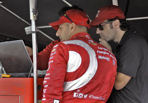 Photo - Driver Tony Kanaan, left, of Brazil and his driver coach Dario Franchitti, of Scotland, look over statistics after a practice run for the IndyCar Firestone Grand Prix of St. Petersburg auto race Friday, March 28, 2014, in St. Petersburg, Fla. The race takes place Sunday afternoon. (AP Photo/Chris O'Meara)