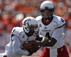 Photo - Cincinnati quarterback Munchie Legaux (4) hands off to running back Ralph Abernathy (1) during the second half of their NCAA college football game against Illinois on Saturday, Sept. 7, 2013, in Champaign, Ill. (AP Photo/Andrew A. Nelles)