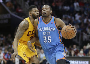 Photo - Oklahoma City Thunder's Kevin Durant (35) is fouled by Cleveland Cavaliers' Alonzo Gee (33) during the third quarter of an NBA basketball game Thursday, March 20, 2014, in Cleveland. Oklahoma City defeated Cleveland 102-95. (AP Photo/Tony Dejak)