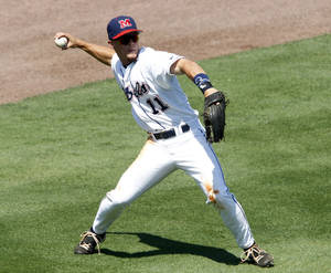 Photo - Mississippi's Braxton Lee throws the ball to third during the eighth inning against Arkansas, during the Southeastern Conference NCAA college baseball tournament Wednesday, May 21, 2014, in Hoover, Ala. (AP Photo/Butch Dill)