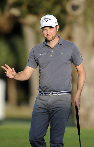 Photo - Chris Kirk waves after sinking a birdie putt on the 18th green during the third round of the McGladrey Classic golf tournament on Saturday, Nov. 9, 2013, in St. Simons Island, Ga. (AP Photo/Stephen Morton)