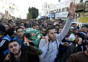 Photo - Palestinians carry the body of Hamza Abu el-Heija, who was killed in a raid by Israeli troops, during his funeral procession, in the West Bank refugee camp of Jenin, Saturday, March 22, 2014. Israeli troops killed at least four Palestinians in an early morning raid that was followed by a clash with angry protesters in a West Bank town on Saturday, the Israeli military and Palestinian security officials said, in the deadliest incident in months. The Israeli military said the raid aimed to arrest Hamza Abu el-Heija, a 22-year-old Hamas operative wanted for involvement in shooting and bombing attacks against Israelis. (AP Photo/Mohammed Ballas)