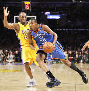 Photo - The Lakers' Kobe Bryant, left, pressures the Thunder's Kevin Durant on Tuesday. AP photo