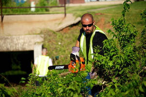 Photo - Former inmate Matthew Izaguirre, a Center for Employment Opportunities participant, clears trees in Moore damaged in last year's tornado. Photo provided <strong></strong>