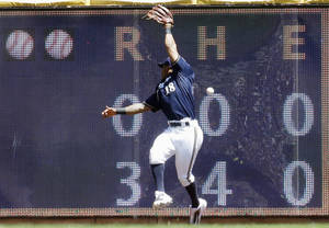 Photo - Milwaukee Brewers left fielder Khris Davis can't catch a ball hit by Colorado Rockies' Brandon Barnes during the second inning of a baseball game Sunday, June 29, 2014, in Milwaukee. (AP Photo/Morry Gash)
