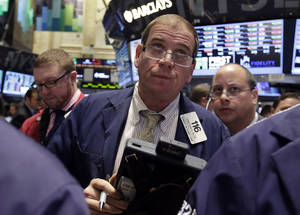 Photo - Trader Jonathan Niles, center, works on the floor of the New York Stock Exchange, Friday, Oct. 25, 2013. Earnings gains from Microsoft and other big U.S. companies are pushing the stock market higher in early trading. (AP Photo/Richard Drew)