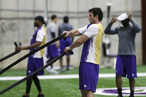 Photo - Minnesota Vikings quarterback Christian Ponder, right, and wide receiver Jerome SImpson, left, work on a rope pull exercise during conditioning workouts for the NFL football team, Wednesday, May 1, 2013 in Eden Prairie, Minn. Uncovering his head to watch is wide receiver Greg Jennings, right. (AP Photo/Jim Mone)