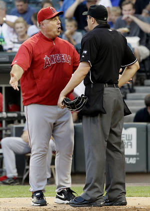 Photo -   Los Angeles Angels manager Mike Scioscia, left, argues with home plate umpire Lance Barrett during the first inning of a baseball game against the Chicago White Sox in Chicago, Friday, Aug. 3, 2012. (AP Photo/Nam Y. Huh)