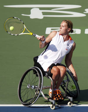 Photo -   FILE - In this Sept. 15, 2008, file photo, Esther Vergeer of the Netherlands, returns a shot during the wheelchair tennis women's doubles open final at the Beijing 2008 Paralympic Games in Beijing, China. After more than 13 years at No. 1 in the wheelchair tennis rankings and going unbeaten since 2003 with 465 consecutive victories, Vergeer entered the London Paralympics with a solid argument for being the most dominant athlete within a single sport. The 31-year-old Dutchwoman extended that run to 468 matches with a 6-1, 6-0 win against Thailand's Sakhorn Khanthasit in the quarterfinals, Tuesday, Sept. 4, 2012. (AP Photo/Ng Han Guan, File)