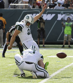 Photo - New York Jets' Nick Folk (2) kicks a 30-yard field goal as Robert Malone (3) holds in the second half of an NFL football game against the Tampa Bay Buccaneers, Sunday, Sept. 8, 2013, in East Rutherford, N.J. (AP Photo/Bill Kostroun)