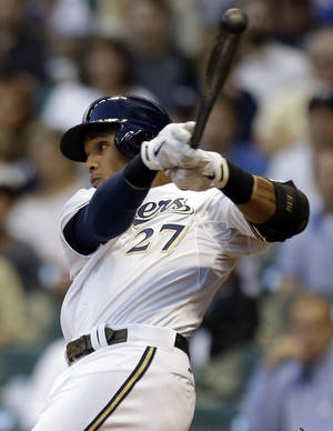 Photo - Milwaukee Brewers' Carlos Gomez watches his two-RBI double against the San Diego Padres during the third inning of a baseball game on Wednesday, July 24, 2013, in Milwaukee. (AP Photo/Jeffrey Phelps)