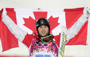 Photo - Canada's Alex Bilodeau celebrates after winning the gold medal in the men's moguls final at the 2014 Winter Olympics, Monday, Feb. 10, 2014, in Krasnaya Polyana, Russia.  (AP Photo/Andy Wong)