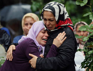 Photo - Mourning relatives cry during the burial for one of the 46 victims killed in Saturday explosions in Reyhanli, near Turkey's border with Syria, Sunday, May 12, 2013. The bombings on Saturday marked the biggest incident of cross-border violence since the start of Syria's bloody civil war and has the raised fear of Turkey being pulled deeper into the conflict.(AP Photo/Burhan Ozbilici)