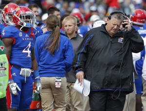 Photo - Kansas coach Charlie Weis, right, removes his head set during the second half of an NCAA college football game against Texas Tech in Lawrence, Kan., Saturday, Oct. 5, 2013. (AP Photo/Orlin Wagner)