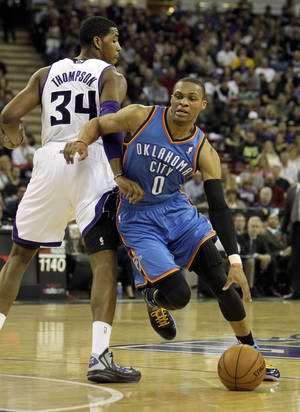 Photo - Oklahoma City Thunder guard Russell Westbrook, right, drives past Sacramento Kings forward Jason Thompson during the first quarter of  an NBA basketball game in Sacramento, Calif., Friday, Jan. 25, 2013. (AP Photo/Rich Pedroncelli) ORG XMIT: SCA104