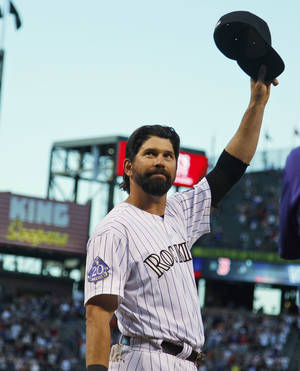 Photo - Colorado Rockies first baseman Todd Helton tips his cap while being honored before his final home baseball game, against the Boston Red Sox, in Denver on Wednesday, Sept. 25, 2013. Helton is retiring at season's end after 17 years with the Rockies. (AP Photo/David Zalubowski)