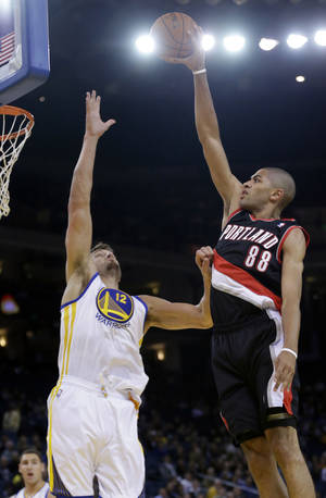 Photo - Portland Trail Blazers' Nicolas Batum (88) shoots over Golden State Warriors' Andrew Bogut during the first half of an NBA preseason basketball game on Thursday, Oct. 24, 2013, in Oakland, Calif. (AP Photo/Marcio Jose Sanchez)