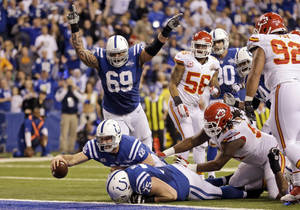 Photo - FILE - In this Saturday, Jan. 4, 2014, file photo, Indianapolis Colts quarterback Andrew Luck (12) dives in for a 5-yard fumble recovery for a touchdown during the second half of an NFL wild-card playoff football game Kansas City Chiefs in Indianapolis. Luck has already beaten Peyton Manning and pulled off the second greatest comeback in playoff history. What does he do for an encore? On Saturday, the second-year quarterback will try to upstage three-time Super Bowl winner Tom Brady, on Brady's home turf.  (AP Photo/Michael Conroy, File)