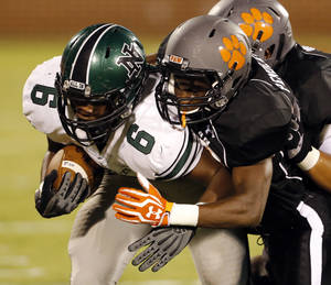 Photo - Norman North's Z'Quan Hogan (6) is pushed out of bounds by Norman High's  Kierstan Pendleton in the second quarter at Gaylord Family-Oklahoma Memorial Stadium in Norman, Okla., on Thursday, Sept. 5, 2013. Photo by Steve Sisney, The Oklahoman