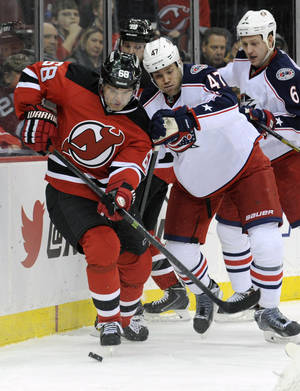 Photo - New Jersey Devils' Jaromir Jagr, left, of the Czech Republic, controls the puck as he is checked by Columbus Blue Jackets' Dalton Prout during the second period of an NHL hockey game on Thursday, Feb. 27, 2014, in Newark, N.J. (AP Photo/Bill Kostroun)