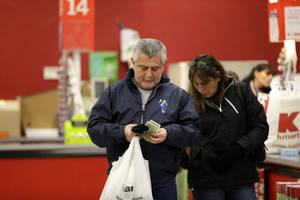 Photo - In this  Thursday, Nov. 28, 2013, photo, a man sorts through cash after checking out at a Kmart, in New York.  The Commerce Department reports how much consumers spent and earned in October on Friday, Dec. 6, 2013.  (AP Photo/Julio Cortez)