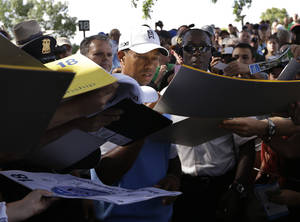 Photo - Tiger Woods signs autographs during a practice round for the PGA Championship golf tournament at Oak Hill Country Club, Tuesday, Aug. 6, 2013, in Pittsford, N.Y. (AP Photo/Charlie Neibergall)