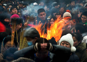 photo - Chinese burn incense as they pray for health and fortune on the first day of the Lunar New Year at Yonghegong Lama Temple in Beijing Sunday, Feb. 10, 2013. Millions across China are celebrating the arrival of the Lunar New Year, the Year of the Snake, marked with a week-long Spring Festival holiday. (AP Photo/Andy Wong)