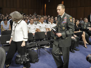 Photo -   FILE - In this June 23, 2011, file photo, Gen. David Petraeus, center, walks with his wife Holly, left, past a seated Paula Broadwell, rear right, as he arrives to appear before the Senate Intelligence Committee during a hearing on his nomination to be Director of the Central Intelligence Agency on Capitol Hill in Washington. Petraeus quit Nov. 9, 2012, after acknowledging an extramarital relationship. As questions arise about the extramarital affair between Petraeus and his biographer, Paula Broadwell, she has remained quiet about details of their relationship. However, information has emerged about Jill Kelley, the woman who received the emails from Broadwell that led to the FBI's discovery of Petraeus' indiscretion. (AP Photo/Cliff Owen, File)