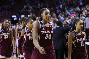 Photo - Texas A&M's Karla Gilbert (34), Texas Tori Scott (15), Curtyce Knox (11), Tavarsha Scott-Williams (32) walk off the court with their teammates following a regional final game in the NCAA college basketball tournament in Lincoln, Neb., Monday, March 31, 2014. Connecticut won 69-54. (AP Photo/Nati Harnik)