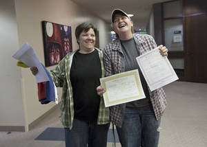 Photo - FILE - This Dec. 20, 2013 file photo shows Elise Larsen, left, and Samantha Christensen, right, displaying their marriage license after being one of the first same sex couples to receive one at the Salt Lake County Clerk's Office in Salt Lake City. Hours after federal judges struck down bans on same-sex marriage in Utah and Oklahoma, activist Evan Wolfson and his colleagues reached out to gay rights groups in the deeply conservative states with both congratulations and a reminder: Court wins alone won't be enough.  (AP Photo/Kim Raff, file)