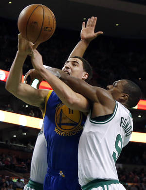 Photo - Golden State Warriors guard Klay Thompson (11) is fouled by Boston Celtics guard Rajon Rondo (9) as he goes up for a shot in the second half of an NBA basketball game in Boston, Wednesday, March 5, 2014. The Warriors won 108-88. (AP Photo/Elise Amendola)
