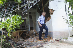 Photo - A Kosovo police officer inspects the damage caused by an explosion that rocked Kosovo's main power plant, in Obilic, Kosovo, Friday, June 6, 2014. A huge explosion rocked Kosovo's main power plant Friday, causing casualties and damaging nearby houses. Police could not immediately confirm whether there were any deaths in the blast Friday at Kosovo A power plant outside the capital Pristina. They say at least a dozen people have been injured. (AP Photo/Visar Kryeziu)